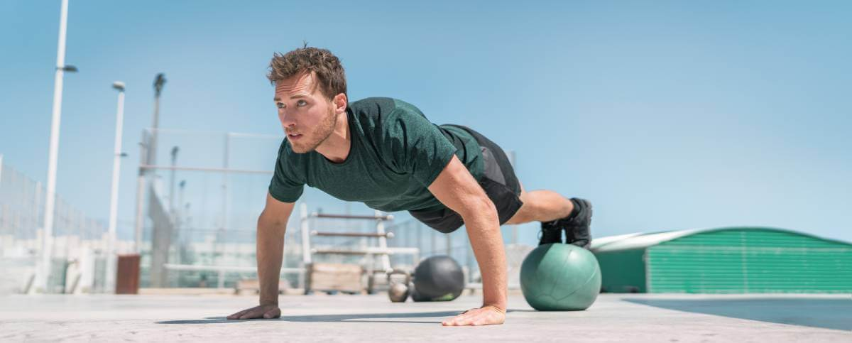 Athlete strength training pushup, balancing legs on medicine ball for advanced core body workout push-ups