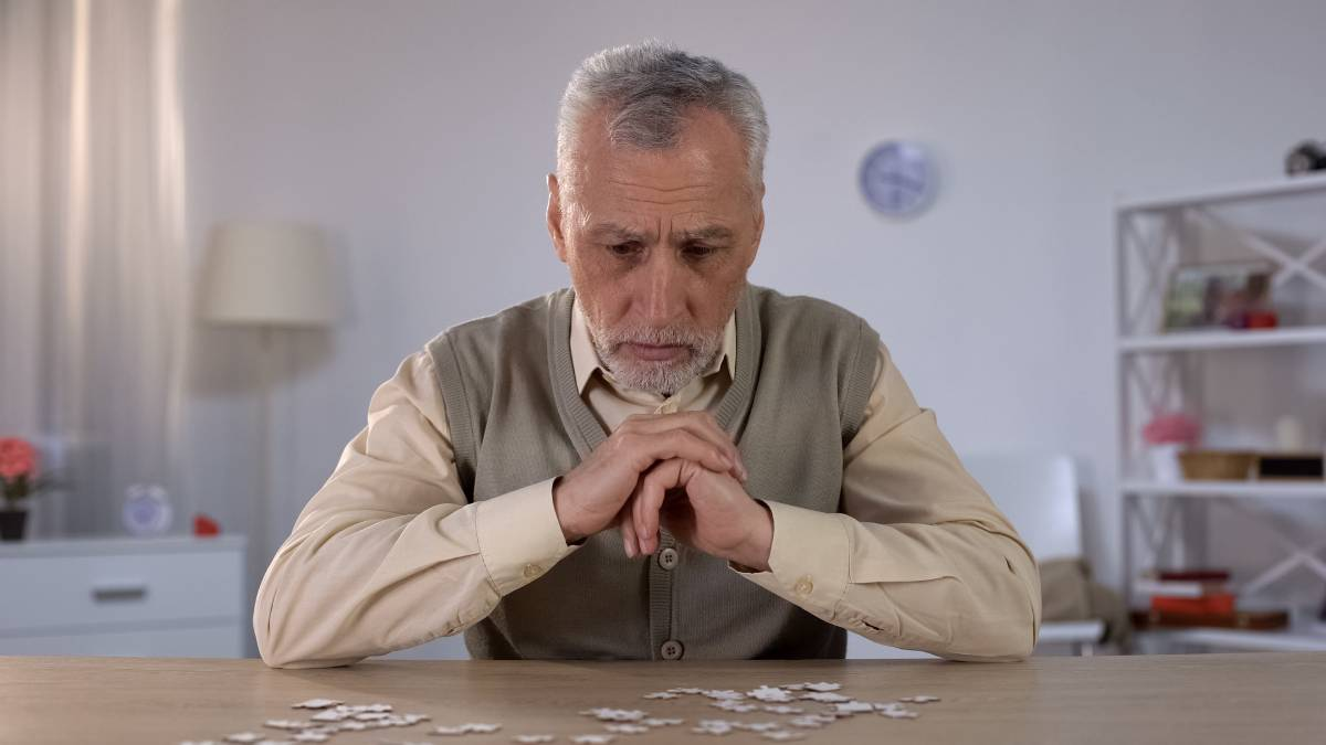 Old man exercises with puzzle