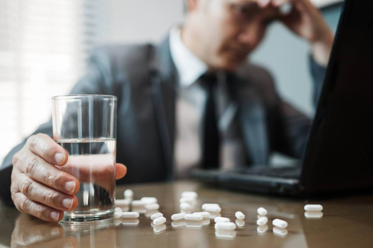Asian Businessman holding glass of water with pills