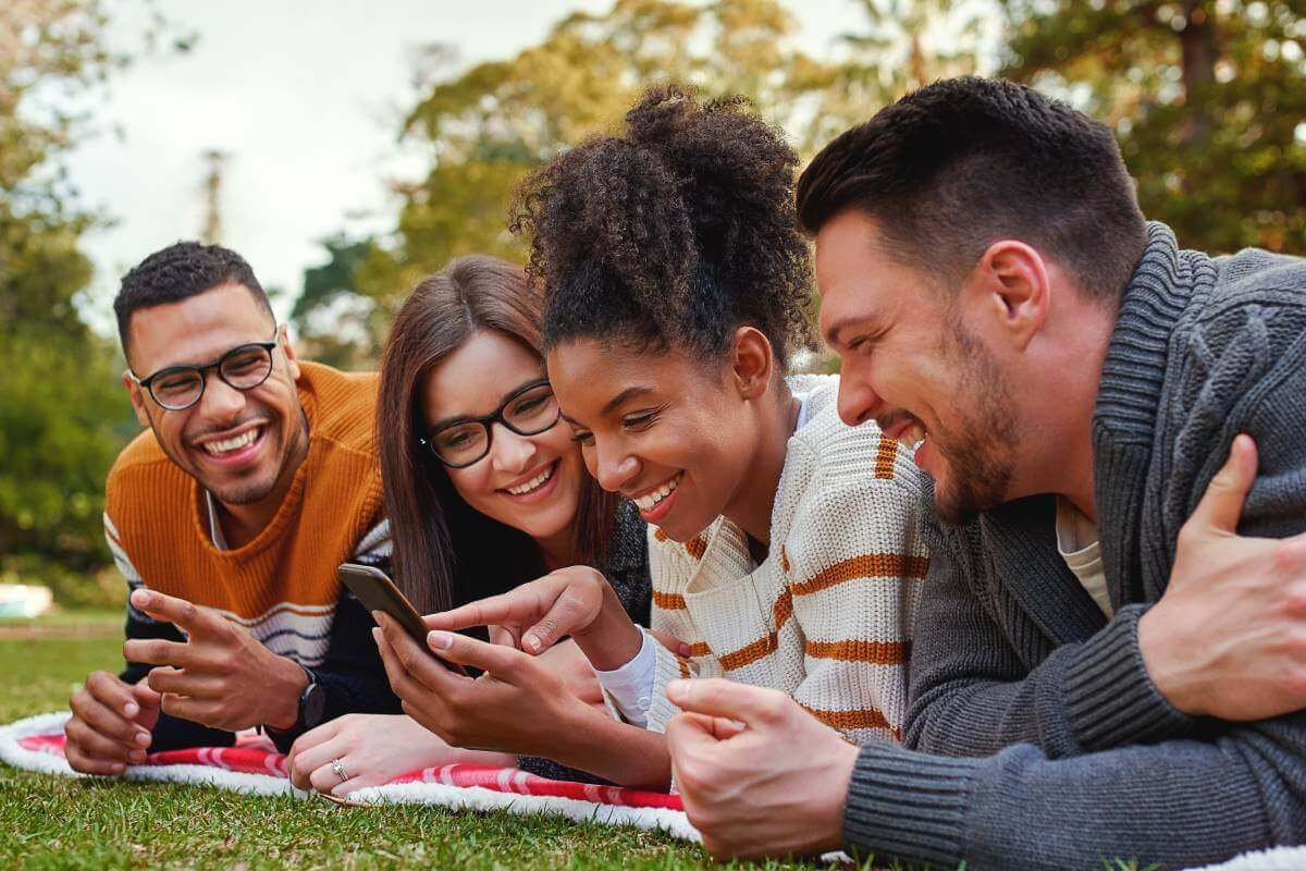 Smiling mixed race group of friends lying together on green grass using mobile phone in the park