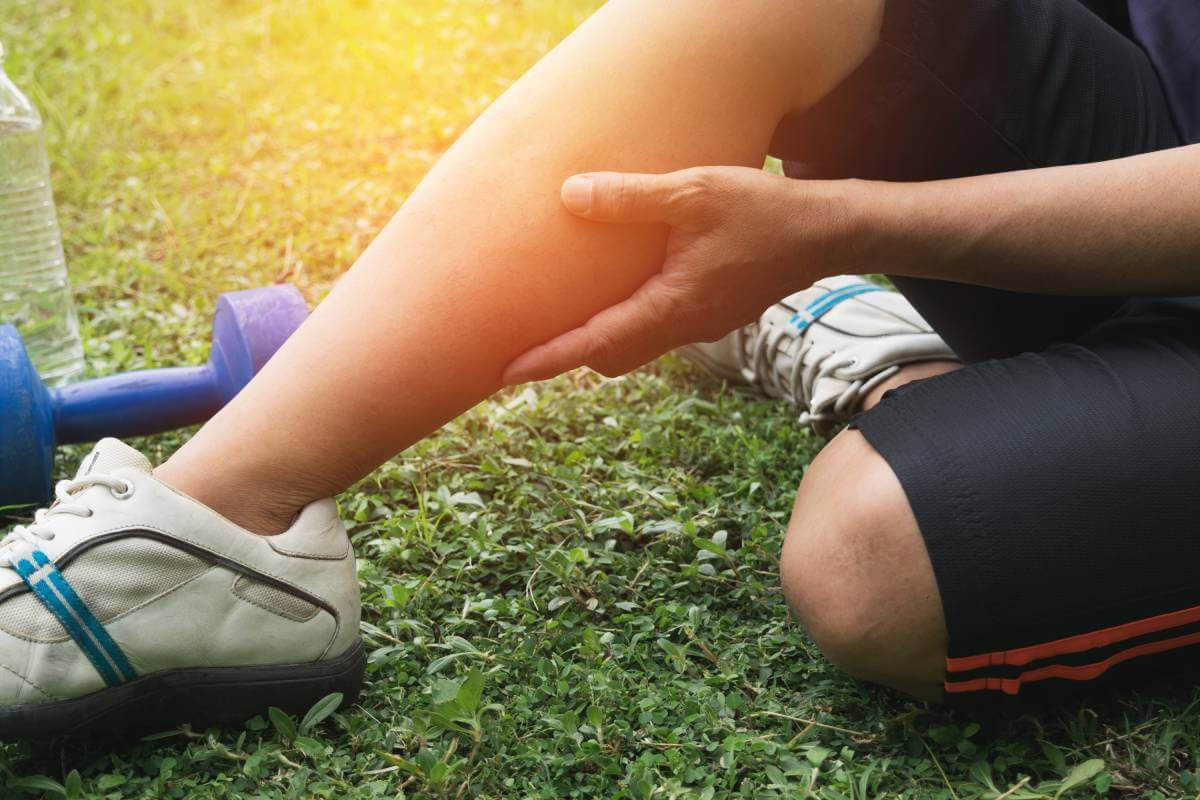 man fill ankle or calf pain during exercise in a day time for sport