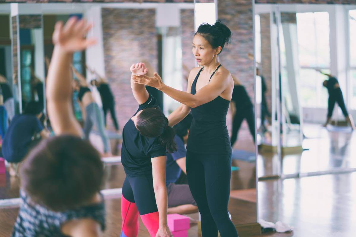 Group women asian doing stretching yoga hot exercises with instructor in studio