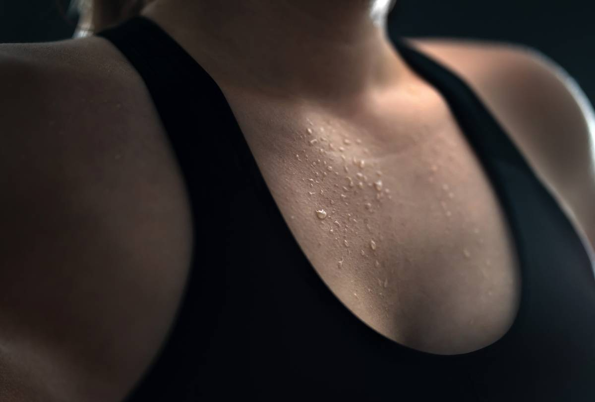 Low key close up of wet female chest with water drops