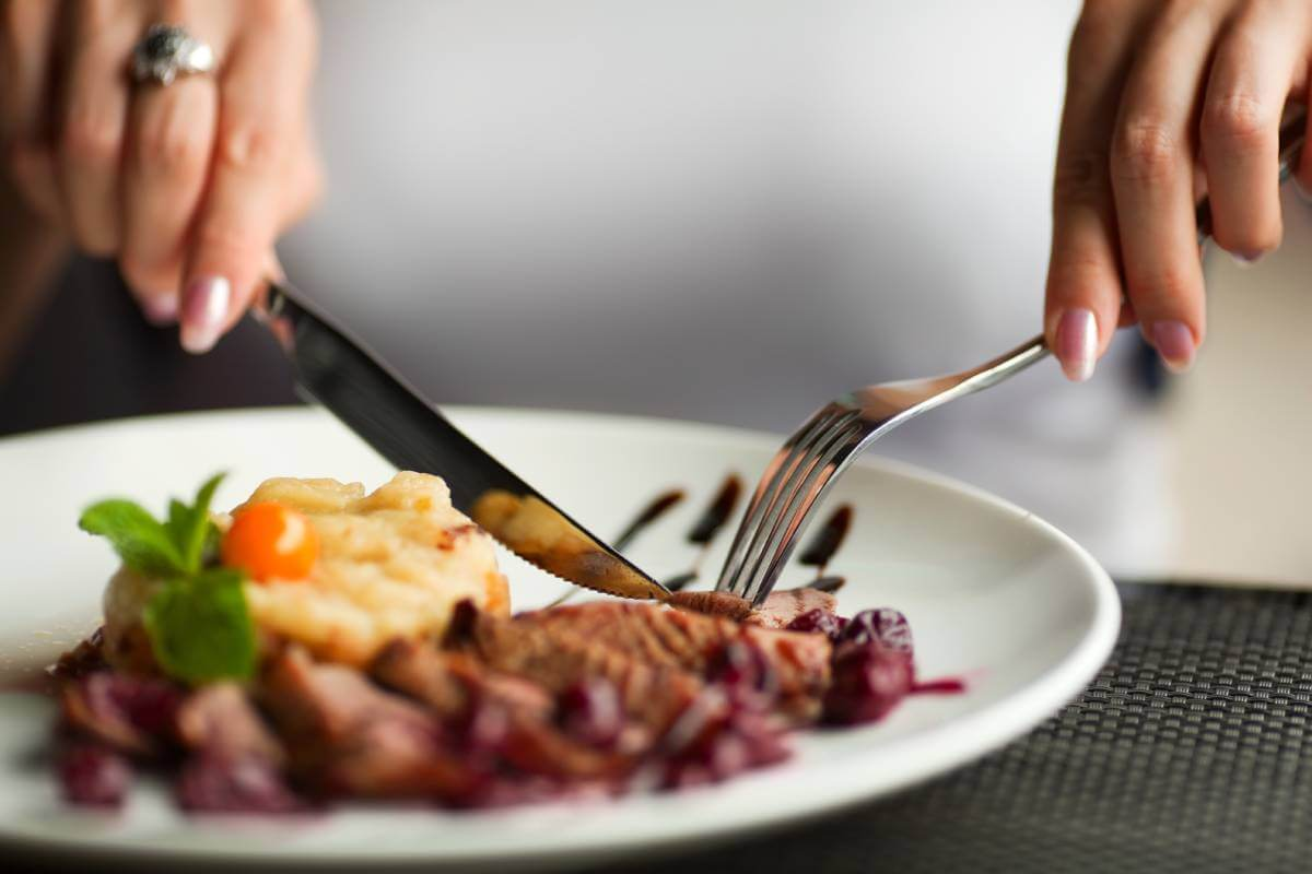 woman dining on meat
