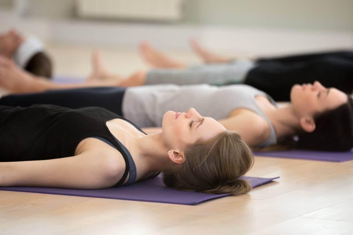 Group of young yogi people practicing yoga lesson, doing Savasana pose