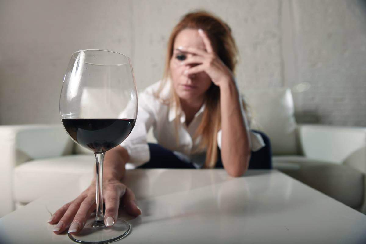 sad depressed alcoholic drunk woman drinking at home