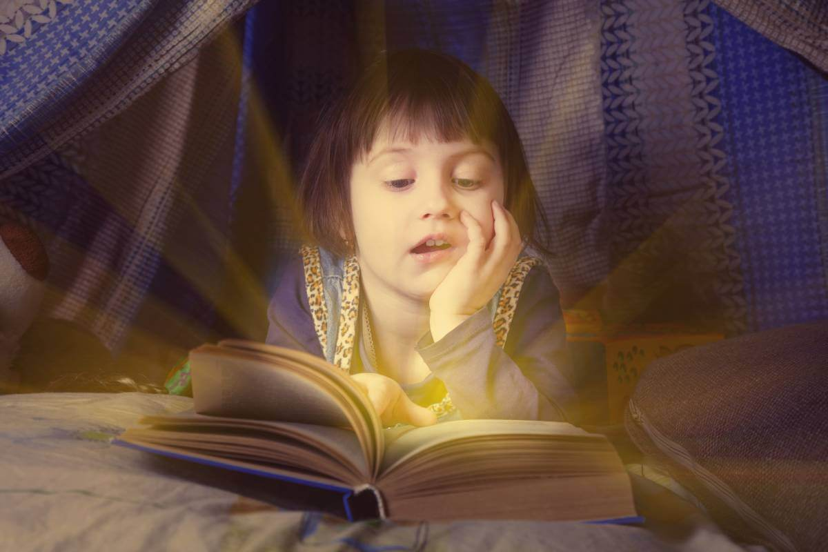 cute little child girl reading a book in bed before going to sleep