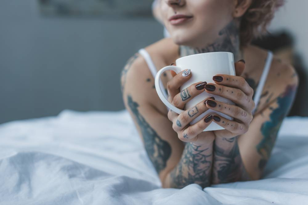 tattooed girl drinking coffee in bed at morning