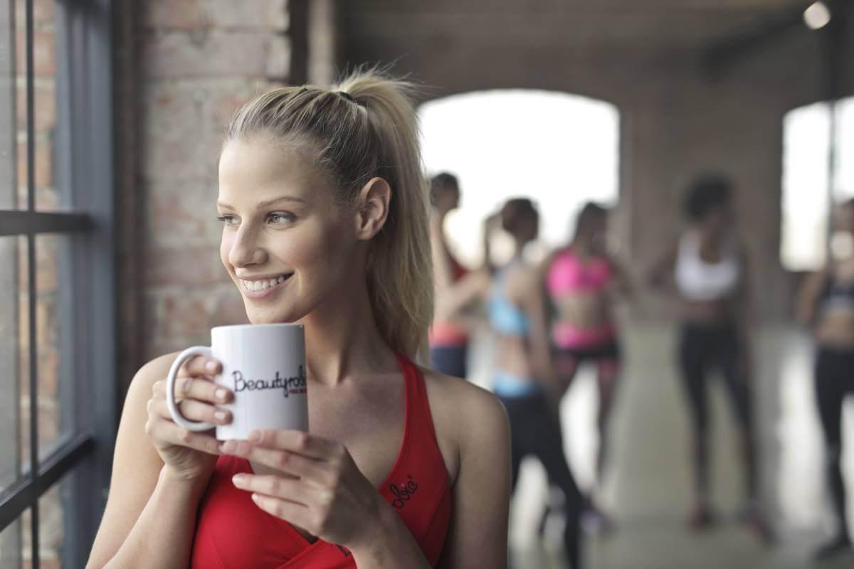 woman holding white ceramic mug while smiling near glass window