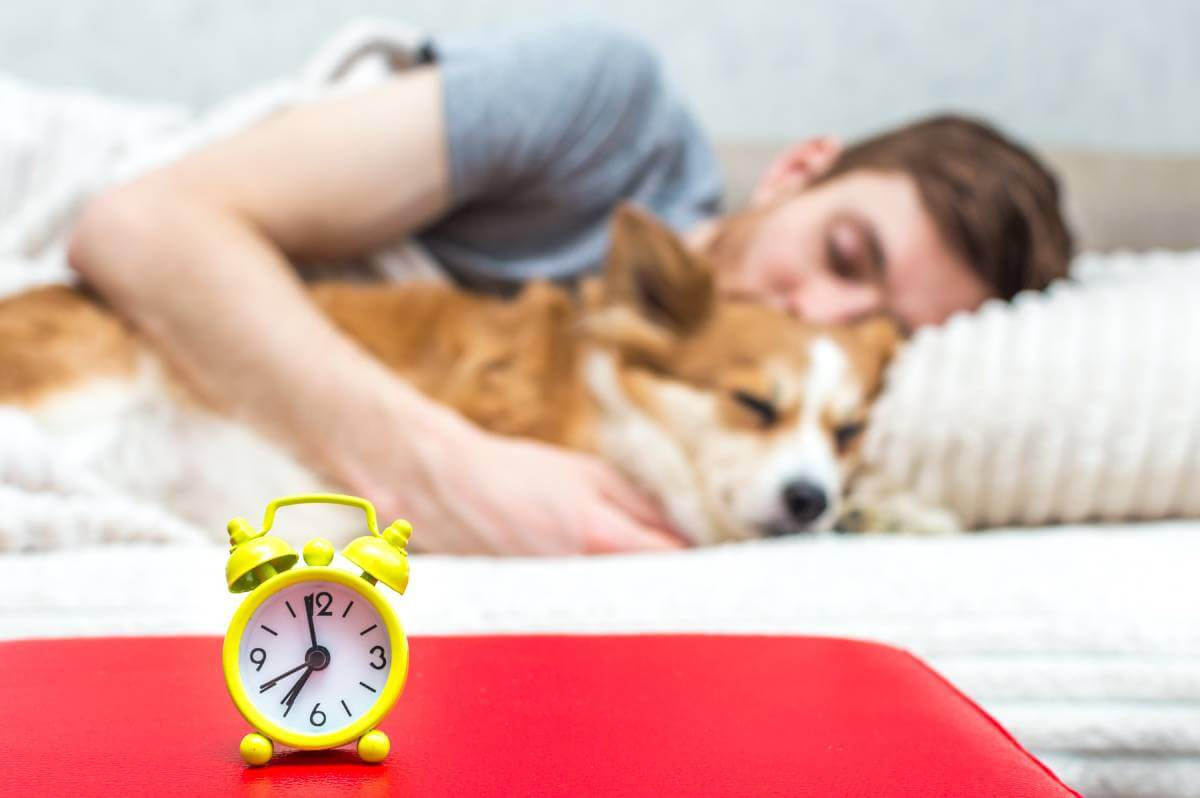 young man and dog are sleeping together behind small clock